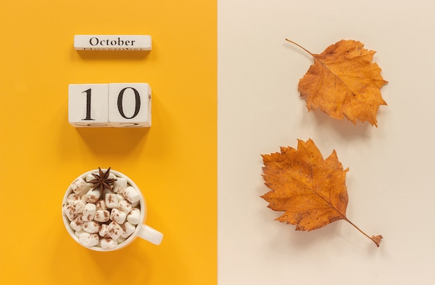 Calendar october 10, cup of cocoa with marshmallows and yellow autumn leaves