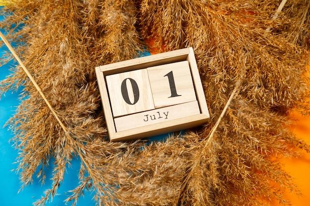 数字と月の木製の立方体のカレンダー。木製のカレンダーで番号を選択します。 7月1日。7月の日付