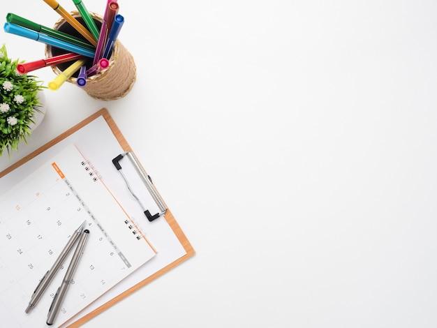 テーブルトップビューの隔離されたコピースペースにペンとカラーペンボックスを備えたドキュメントボード上のカレンダー