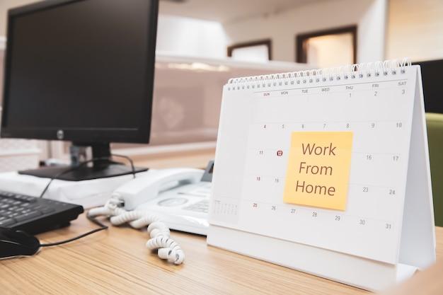 Календарь на столе с бумажной запиской сообщения работы из дома.