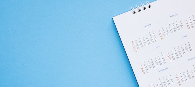 Calendar page close up on blue background business planning appointment meeting concept