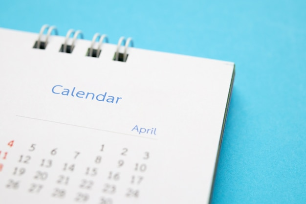 Calendar page close up on blue surface business planning appointment meeting concept
