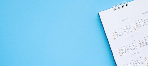 カレンダーページは青い背景のビジネスプランニング予定会議のコンセプトにクローズアップ