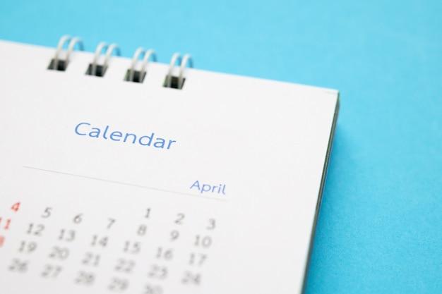 カレンダーページは青い表面の事業計画の予定会議の概念にクローズアップ