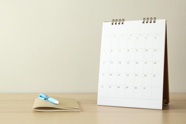 カレンダーページは、ペンとノートブックビジネスプランニング予定会議のコンセプトで木製のテーブルの背景にクローズアップ