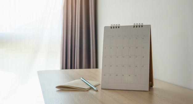 カレンダーページは、鉛筆とノートブックビジネスプランニング予定会議のコンセプトで木製のテーブルの背景にクローズアップ