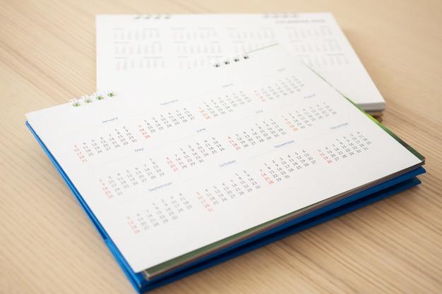 Страница календаря заделывают на деревянный стол. концепция встречи встречи бизнес-планирования