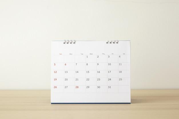 白い壁の背景事業計画の予定会議の概念と木のテーブルにカレンダーページをクローズアップ