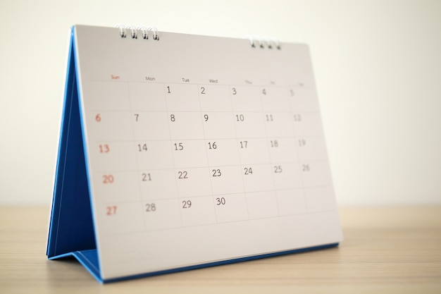 カレンダーページは白い壁と木製のテーブルにクローズアップ