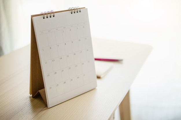 Calendar page close up on wood table with pen and notebook business planning appointment meeting concept