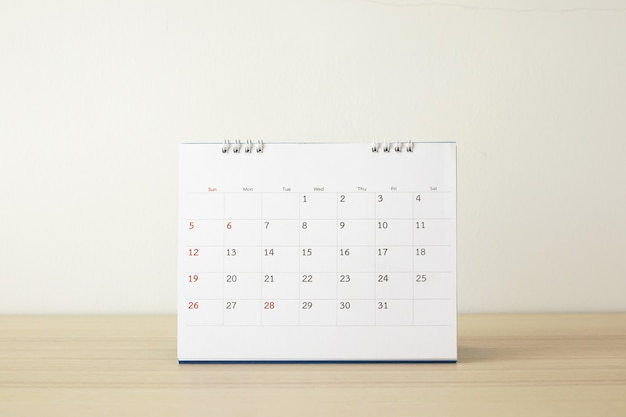 Calendar page close up on wood table with white wall background business planning appointment meeting concept