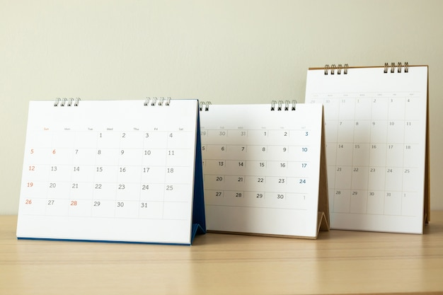 Calendar page close up on wood table with white wall background