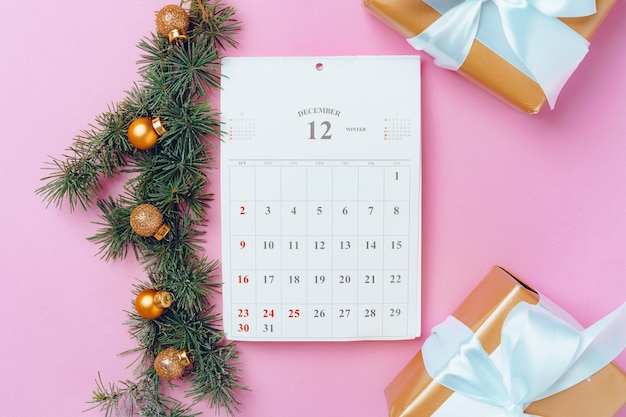 Calendar page of december with festive decorations on pink