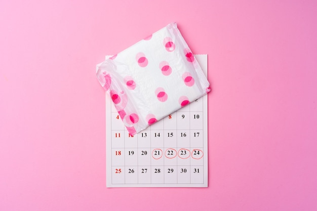 Calendar page and female hygienic pad on pink background top view
