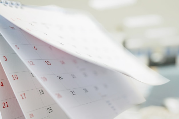 Calendar page flipping sheet close up on office table interior background business schedule planning appointment meeting concept