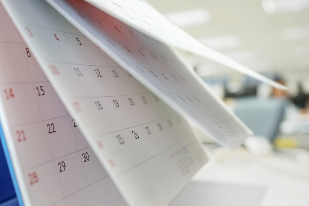 ぼやけたオフィスインテリア背景ビジネススケジュール計画予定会議のコンセプトとテーブルの上のカレンダーページめくりシート