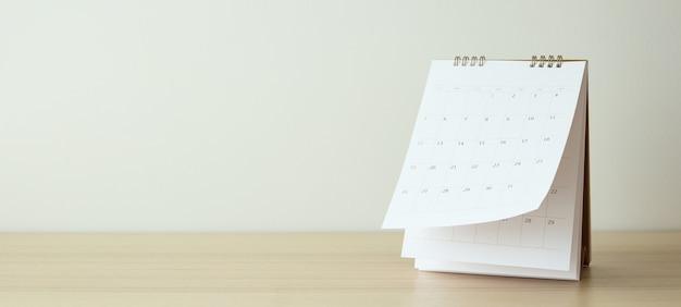 Страницы календаря переворачивают лист на фоне деревянного стола.