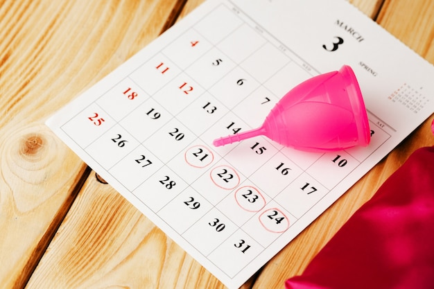 Calendar page and menstrual cup close up on table