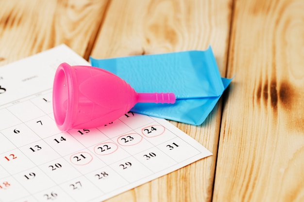Calendar page and menstrual cup close up