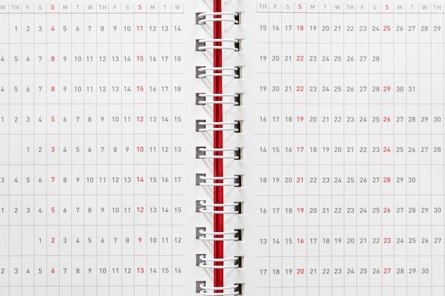 ノートブックの赤い表紙のカレンダーページ