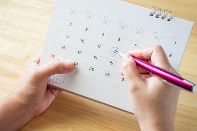 机のテーブルにペンを持っている女性の手でカレンダーページ
