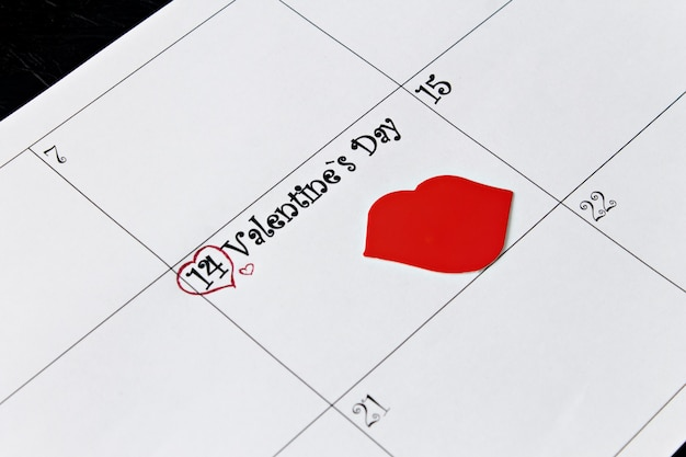 Calendar page with lips on february 14, valentine's day on a black background.