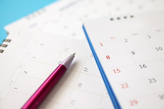 Calendar page with pen close up on blue background business planning appointment meeting concept