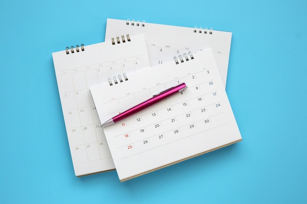 Calendar page with pen close up on blue table, business planning appointment meeting concept