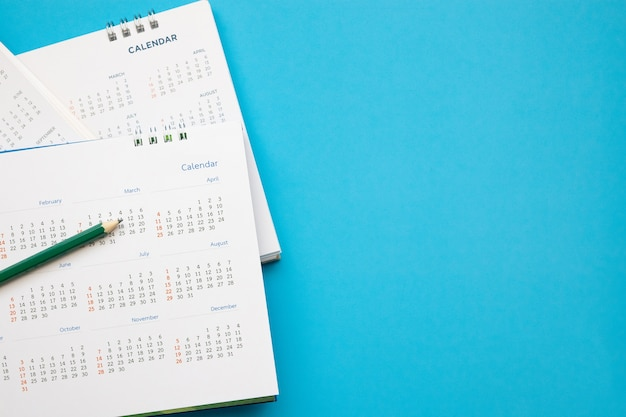 Calendar page with pencil close up on blue background business planning appointment meeting concept