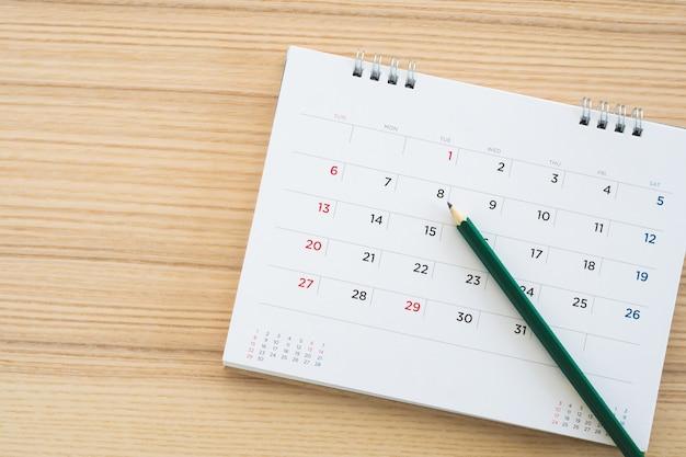 Страница календаря с карандашом на деревянном столе