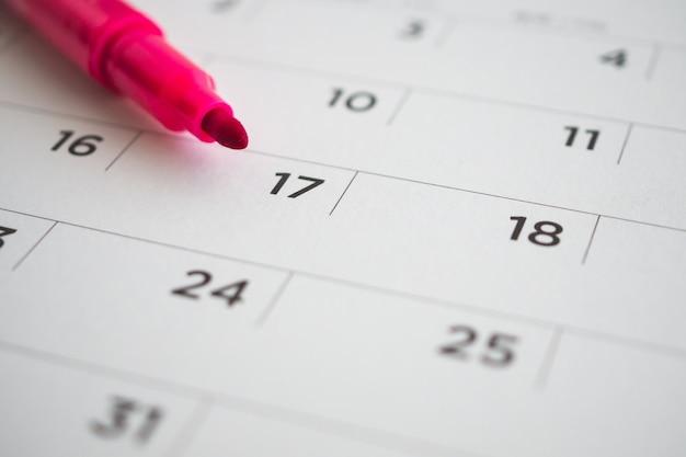Страница календаря с красной ручкой крупным планом