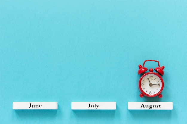 Calendar summer months and red alarm clock over august on blue. concept august time