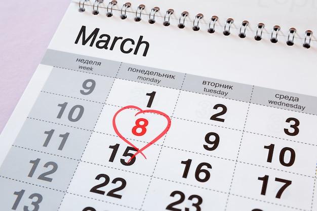 Календарь с красной датой 8 марта. дни недели написаны на английском и русском языках.