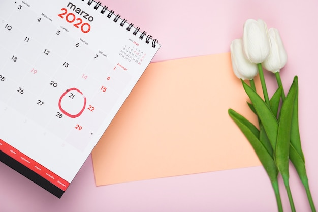 Calendar with card and tulips bouquet