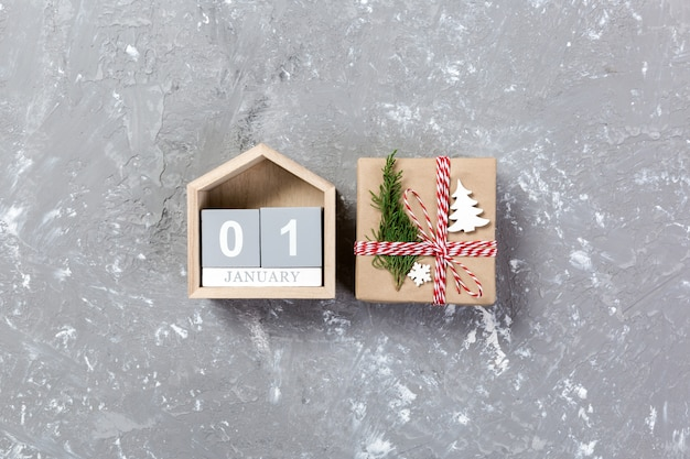 Calendar with date 1 january and gift boxes on concrete