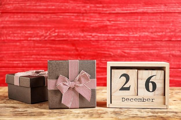 Календарь с датой и подарочными коробками на цветном фоне. рождественское понятие