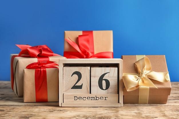 Календарь с датой и подарочными коробками на цветной стене. рождественское понятие