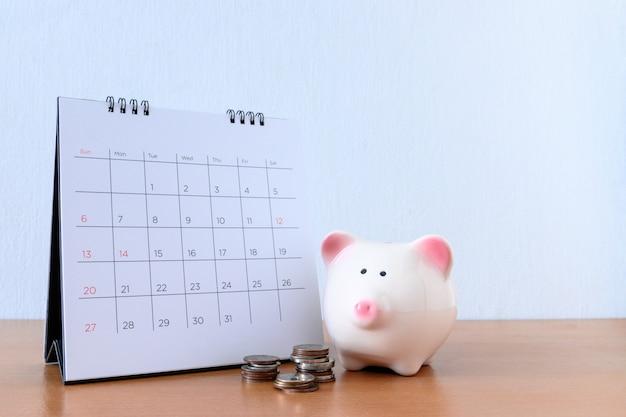 日と木のテーブルにpiggybankのカレンダー