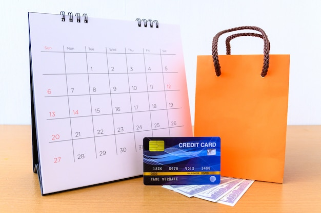 Calendar with days and credit card and orange paper bag on wood table. shopping concept