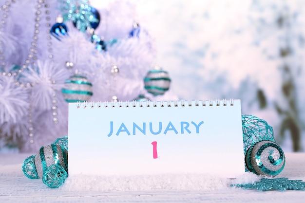 Календарь с новогодними украшениями на зимнем фоне