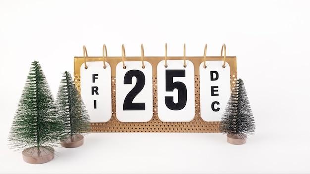 Календарь с датой 25 декабря, зеленые елки на белом