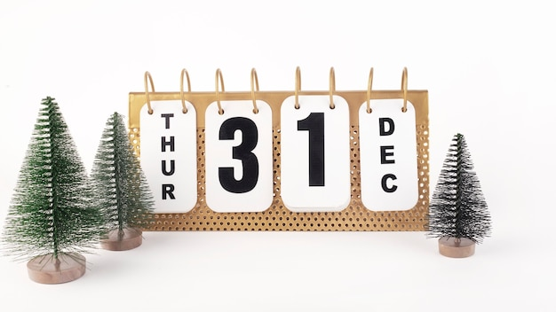 Календарь с датой 31 декабря, зеленые елки на белом