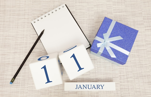 Calendar with trendy blue text and numbers for january 11th and a gift in a box