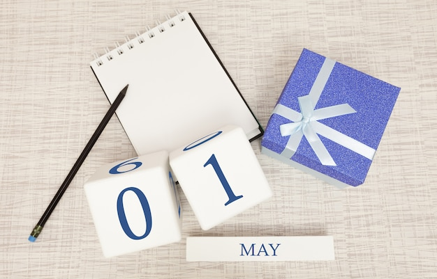 Calendar with trendy blue text and numbers for may 1 and a gift in a box.