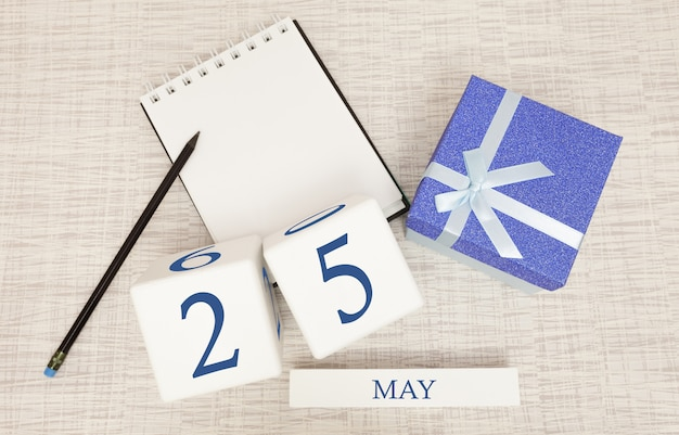 Calendar with trendy blue text and numbers for may 25 and a gift in a box.