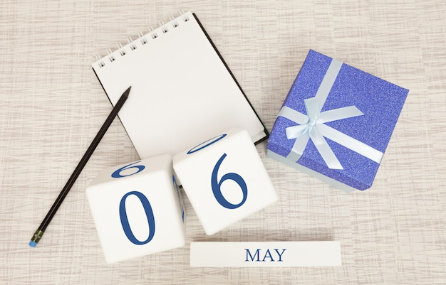 Calendar with trendy blue text and numbers for may 6 and a gift in a box.