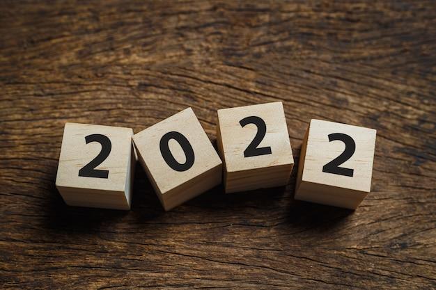 カレンダー木製キューブブロック2022年、木製の背景、新年の目標を前向きに開始します。 12月から1月。
