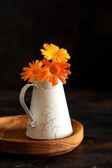 검은 배경에 작은 꽃병에 금송화 꽃다발.