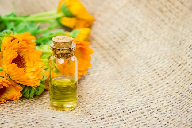 Calendula extract and flowers in a small bottle.