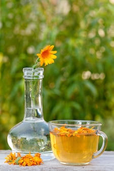 유리 플라스크에 줄기가 있는 금송화 꽃과 옆에 같은 꽃, 흐릿한 녹색 자연 배경을 가진 나무 판자에 차 한 잔